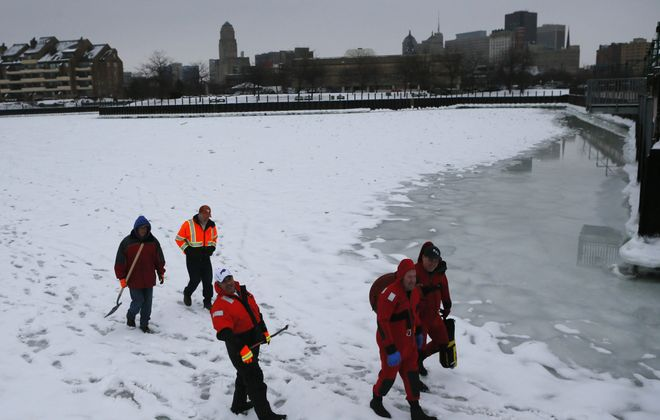 City engineers and firefighters from Buffalo's Rescue One walk off after taking measurements of the thickness of the ice in Erie Basin Marina earlier this week.