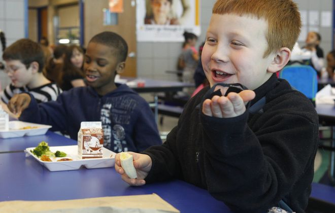 Eight-year-old Noah Licht, foreground, enjoys a conversation with classmates during lunch period at Niagara Street Elementary School in Niagara Falls. Not only lunch, but breakfast, too, is offered to every student in seven schools that qualify for the USDA's new program.