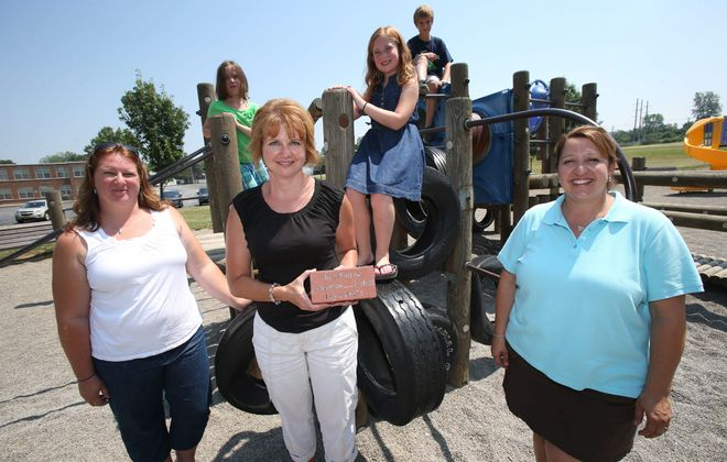 Cloverbank Playground Committee members from left, Jeannie Reigle, Janice Shaver and Michele Grime stand near the old playground where from left, Emily Buil, 8, and Megan, 8, and Michael Reigle, 10, play on Wednesday.