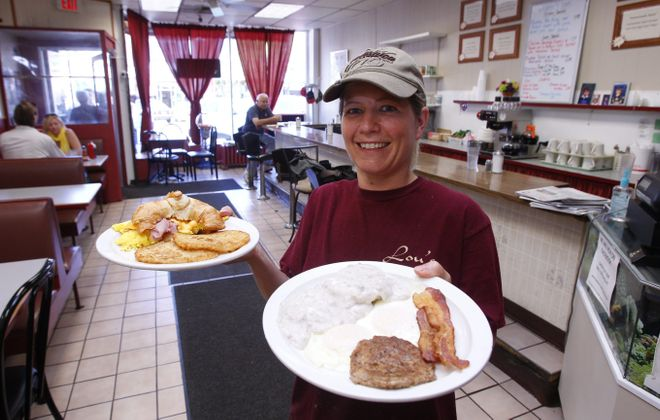 Waitress Donna Watkins carries a breakfast croissant sandwich and Southern special at Lou's Restaurant.