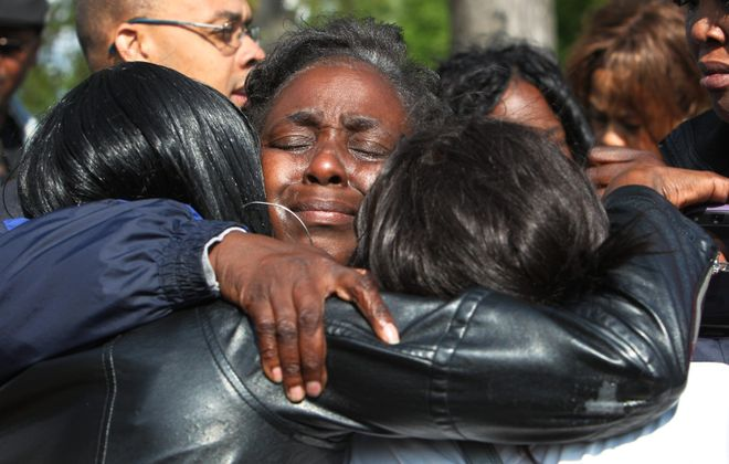 Nina Baskin hugs her daughters hours after her son, Marquayle Lee, was killed in a shooting in Martin Luther King Park last May. Four others were wounded in the shooting. (Sharon Cantillon / Buffalo News file photo)