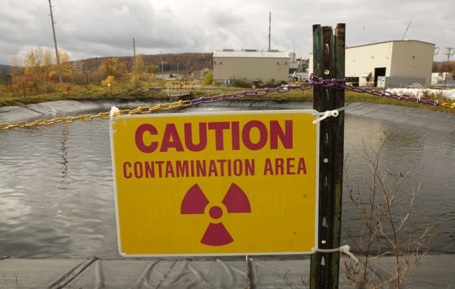 A sign warning of radioactive contamination is posted at a holding pond where treated wastewater is stored to be tested before it is released at the West Valley Demonstration Project.