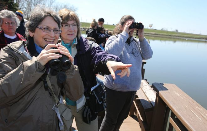 Joan O'Brien, of the Town of Tonawanda, left, and Peg Clukey, of Williamsville, look for birds from a deck at Tifft Nature Preserve in Buffalo, during a class for amateur bird-watchers Sunday.