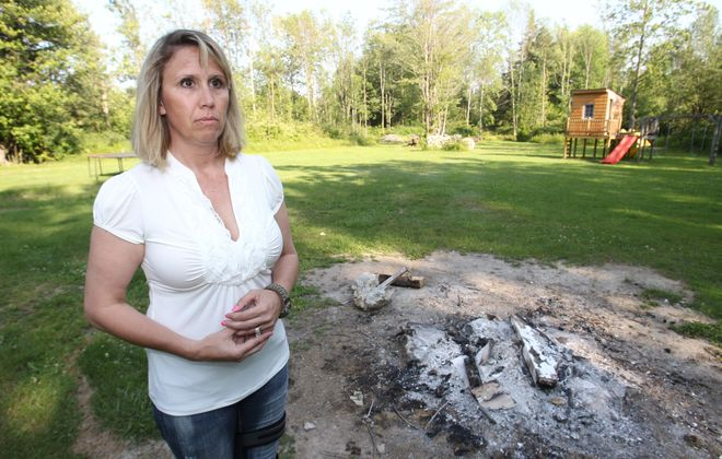 Debi Weber, mother of a 17-year-old girl left alone for a weekend, stands near a fire pit where some of her belongings were set on fire during an unauthorized party at her home.
