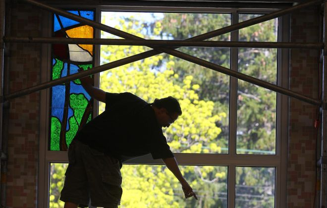 """Workers install the """"Song of Creation"""" window designed by Sister Ann Therese Kelly in a wall near the library at Villa Maria College. The window was inspired by St. Francis of Assisi's """"The Canticle of the Sun."""" """"It's a transformational poem,"""" she says."""