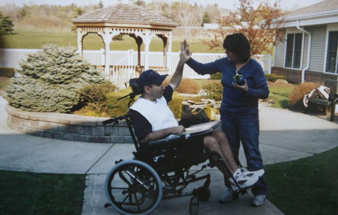 Donald J. Herbert gives his wife, Linda, a high-five a week after waking up in April 2005. He suffered a brain injury fighting a fire in December 1995 and emerged from a minimally conscious condition 10 years later.