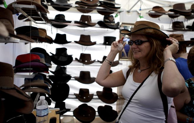 Kathy Hanson tries on several hats during the Allentown Art Festival. Organizers estimate this year's attendance at about 150,000.
