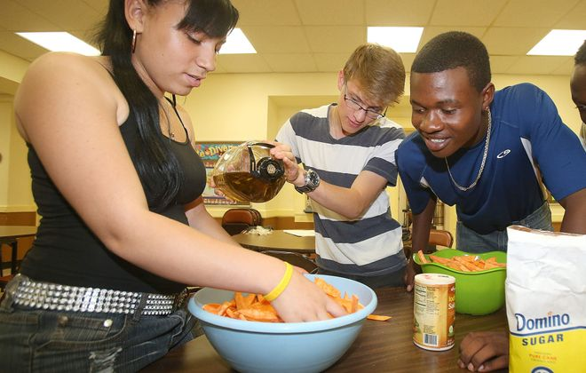 From left, Mariah Waller, 14, Nick Cannistraci, 22, and Donacian Nidaruta, 14, mingle sweet potatoes and olive oil in the kitchen at Pilgrim St. Luke's Church, at Richmond Avenue and West Utica Street in Buffalo on Aug. 9. The Growing Green program, part of the  Massachusetts Avenue Project, demonstrates cooking healthy foods to promote healthier eating habits among West Side families.  Robert Kirkham/Buffalo News