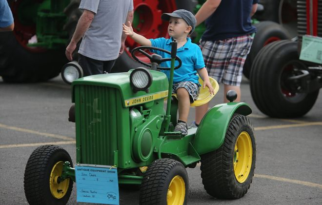 Bradley Milligan, 3, of Cheektowaga, looks ready to drive  Wednesday as he sits on a tractor on the first day of the Erie County Fair in Hamburg.