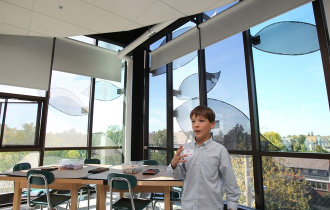 """Fourth-grader John Van Vessem provides tour of renovations at Olmsted School 64 at Thursday's """"grand reopening."""" They include skylights and glass block floors in hallways to let in natural light as well as large windows with a leaf design on the exterior, which reflects the importance of nature in Olmsted's designs. Photo gallery at BuffaloNews.com."""