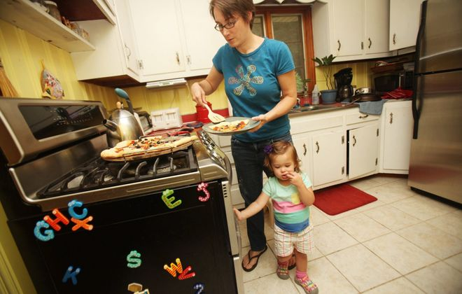 Jo Ehlers hangs around the kitchen as her mom, Andrea Weigl, serves pizza she made for dinner at their home in Raleigh, N.C.