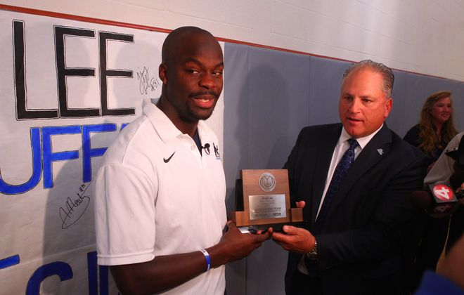 UB wide receiver Fred Lee receives the AllState AFCA Good Works Trophy from UB coach Jeff Quinn at Starpoint High School.