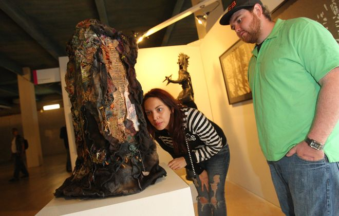 "Kayla Philo, left, and Jared Barto of Elmira look at ""Enchanted Forest 2,"" a mixed media piece by Nancy Belfer, at the third annual Echo Art Fair at the Central Library on Saturday."