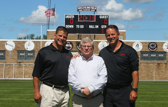From left, Lancaster High Athletic Director Brian Wild, booster club president Patrick Farruggio and coach Chris Dickson stand below the team's new scoreboard, funded by the booster club, that makes its debut on Friday.