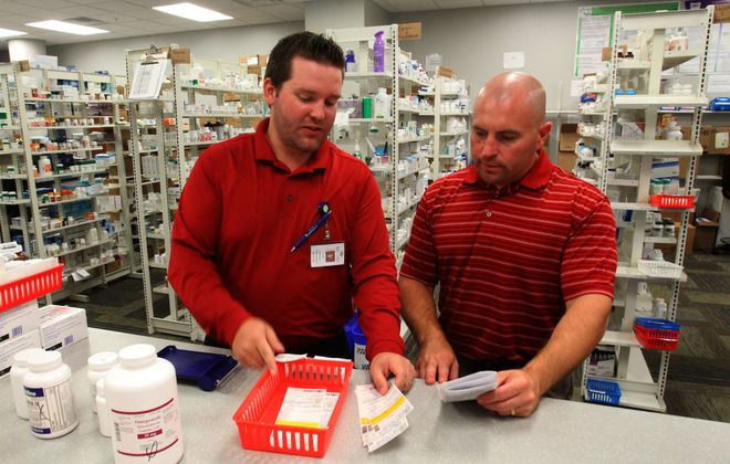 Patrick Comerford Jr., left, and Ken Andrus, both co-owners of Mobile Pharmacy Solutions, work to sustain their unusual business model.