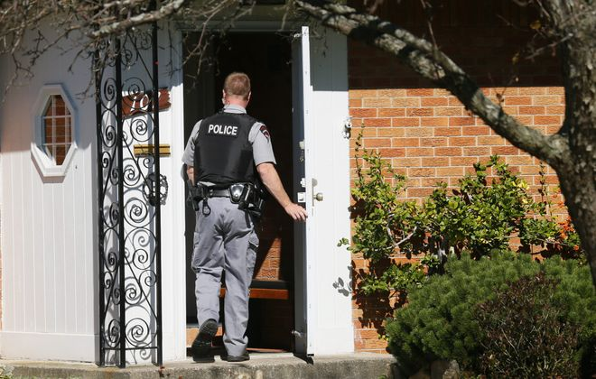 Amherst police detective prepares to enter the home at 107 Dawnbrook Lane on Friday, where an elderly man and woman were found dead in an apparent murder-suicide.