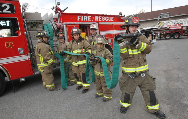 Explorers, junior explorers and Boy Scouts take part in an exercise Saturday at the Angola Volunteer Fire Department. Adviser Tony Carlson, left, watches as Daniel Fosdick, 14, Hannah Russell, 16, Nicholas Czyz, 11, and Seth Tolsma, 12, unspool a fire hose. Standing at rear is Angola Chief Chuck Carlson, who is also committee chairman for Explorer Club Post 735.