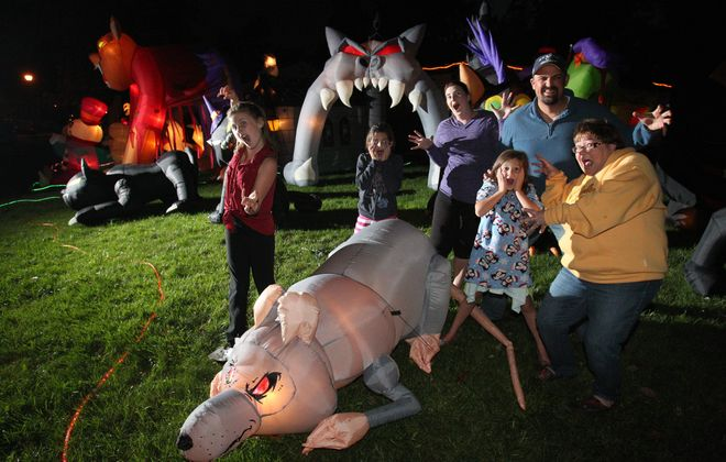 The Siriani family, from left, Miah, 10, Avah, 9, Amy, Myrandah, 6, and Michael, along with neighbor Bella Bolt, react in mock horror to the array of inflatable Halloween decorations filling the Siriani's Town of Tonawanda yard.