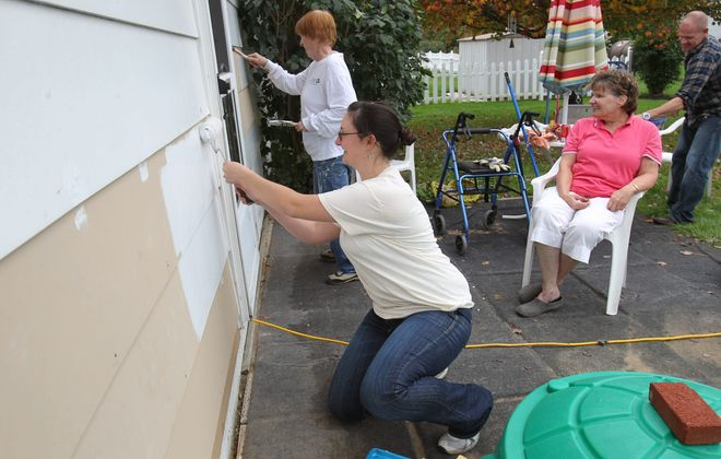 "Volunteers take part in a ""mini-makeover"" Saturday at the Blasdell home of Patricia Ceccarelli, seated, who has multiple sclerosis. Painting the siding are Christy Missico, foreground, and Marilyn Putnam. Mark Rand, who works at Sam's Club, works behind Ceccarelli."