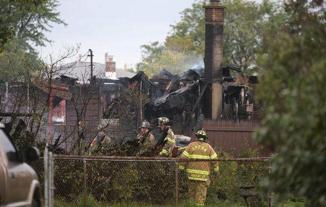 Firefighters finish their work at a house on Fries Road in Town of Tonawanda that was the center of a 7-hour drama in which owner Joe Hollywood, 60, set the blaze during apparent domestic dispute. His body was found there late Monday afternoon.