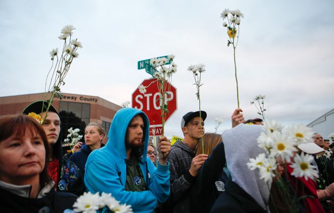 """Protestors hold daisies at the """"Justice for Daisy"""" rally in Maryville, Mo., on Tuesday on behalf of Daisy Coleman, a girl who says she was sexually assaulted when she was 14."""