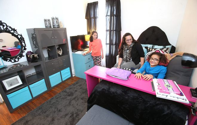Natalie Rivera, 15, right, with her mom, Ericka Galeano, center, and sister, Daliana Rivera, 11, left, sits behind her custom-made desk in her redecorated room in Buffalo on Tuesday.