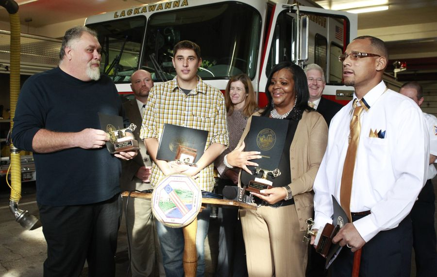 Jack Pirowski, left, and his son, Zachary, are joined by Carmen and Robert Lowe as they describe saving a family from a fire. They were honored as Erie County Citizens of the Month for their actions Oct. 16 in a ceremony at the Lackawanna Fire Department on Tuesday. See a video at BuffaloNews.com.