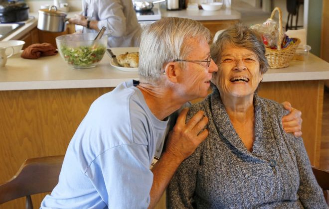 Bill Kelly, 64, gives Jackie Kindl, 81, a hug at lunch in the home they share in Lombard, Ill. They are part of a group of self-sufficient seniors who share the house  in the residential suburban Chicago neighborhood. It is one of four share houses run by the nonprofit Senior Housing Share.