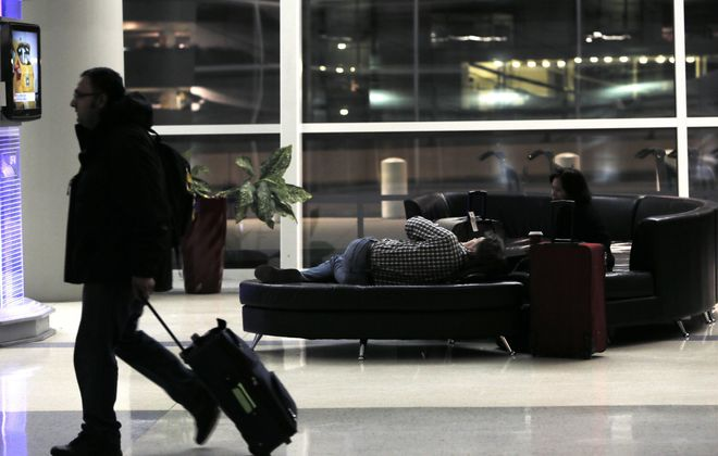 Troy Peoples, center, and Amenia Evernez, right, pass the time watching TV after their flight to Washington State was delayed by two hours due to winter weather at Dallas-Fort Worth International Airport on Monday.