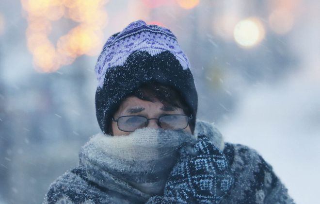 A woman shields herself from the snow while walking on Elmwood Avenue on Dec. 26, 2012