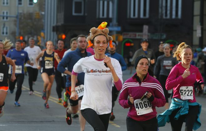 A participant with a turkey hat in the Turkey Trot runs down Franklin Street in Buffalo, Nov. 22, 2012.