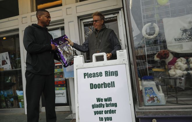 Elmwood Pet Supplies owner John Higgins, right, brings a bag of dog food to customer Jason Chaffin outside the store. (Derek Gee/Buffalo News)
