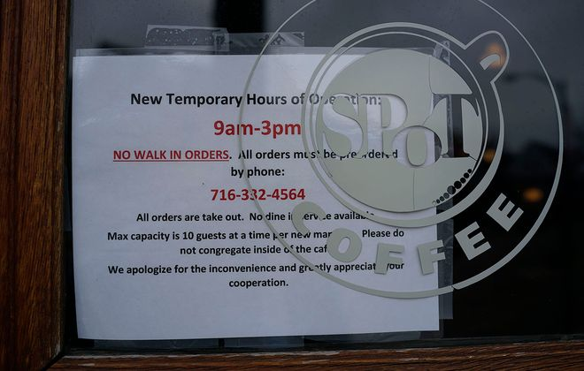 A sign on the front door at Spot Coffee announces that takeout orders may be placed over the phone during reduced business hours, Tuesday, March 17, 2020. (Derek Gee/Buffalo News)
