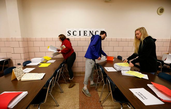 Frontier High School students Emily Marek, left, Chris Contrera, center, and Sarah Steindel, right, pick up learning materials at the school in Hamburg on Tuesday, March 17, 2020. (Mark Mulville/Buffalo News)