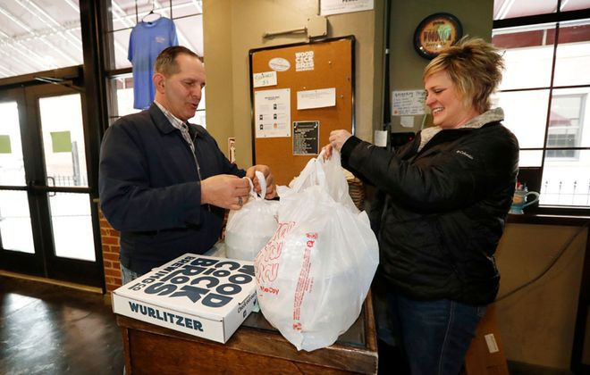 David Bell picks up a takeout dinner from manager Leslie Baker at Woodcock Brothers Brewery at the Wurlitzer Building in North Tonawanda. It is unlikely to pass coronavirus germs through plastic bags or food. (Sharon Cantillon/Buffalo News)