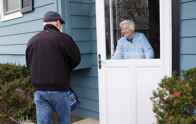 Joe Szychowski brings lunch and dinner to client Charlotte Shultes as he makes his deliveries in West Seneca. (Sharon Cantillon/Buffalo News)