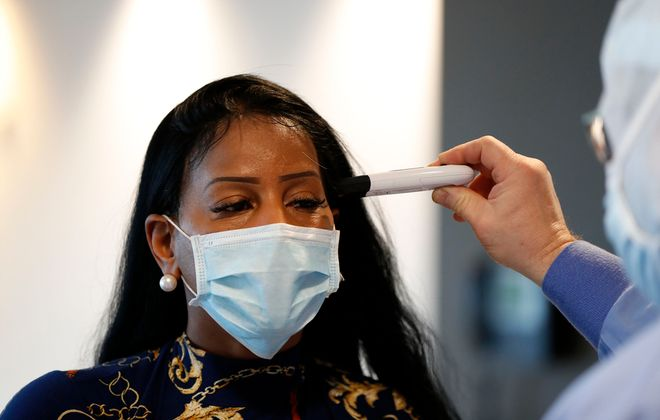 Kent Chittley screens staff member Kimberly Green at an entrance at Kenmore Mercy Hospital on Wednesday, March 18, 2020. (Mark Mulville/Buffalo News)