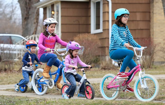 With school out because of COVID-19, the Pahls, from left to right, Elijah, Natalie, Penelope and Maya, ride their bikes in front of their Town of Tonawanda home on Wednesday, March 18, 2020. (Harry Scull Jr./Buffalo News)