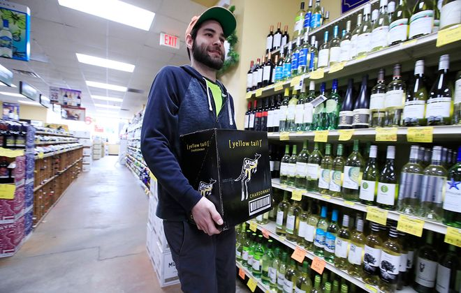 Zach Kindron restocks at the Butler's Wine & Spirits after a busy few days as a result of COVID-19, on Wednesday, March 18, 2020. (Harry Scull Jr./Buffalo News)