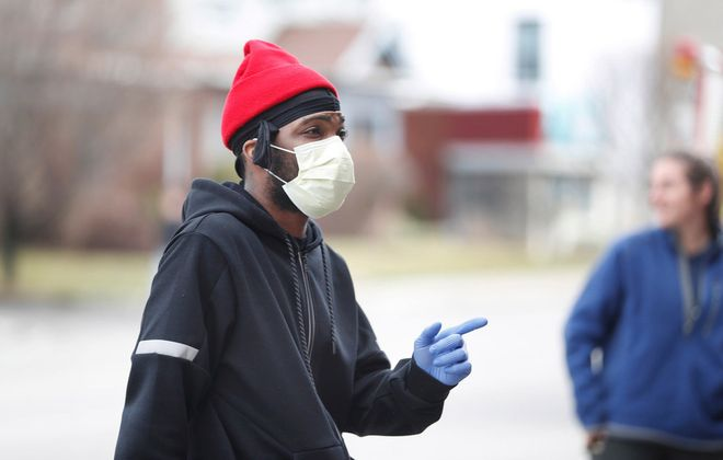 Jordan Goldsmith goes to pick up his paycheck at a restaurant he worked at wearing a mask and latex gloves, Thursday, March 19, 2020. He said his girlfriend is pregnant and he does want to take any chances of getting the coronavirus. (Sharon Cantillon/Buffalo News)