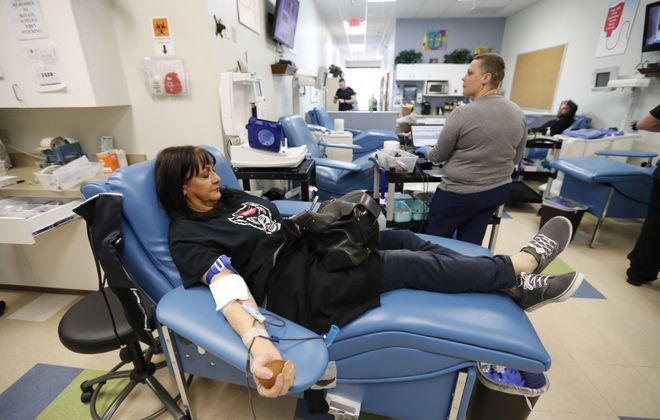 Joan Sullivan looks at her phone as she donates blood at Connect Life in West Seneca on Thursday.       (Mark Mulville/Buffalo News)