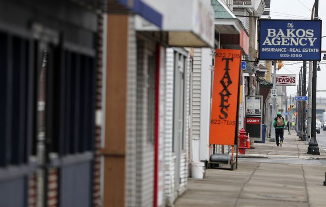 A person walks past the businesses on Clinton Street in Kaisertown in Buffalo Thursday, March 19, 2020. (Mark Mulville/Buffalo News)