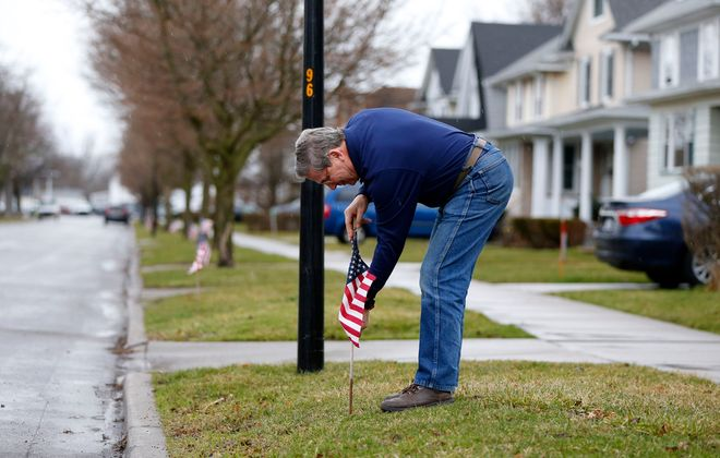 Joseph Riccio places flags in his neighbors yards in Kenmore Friday. (Mark Mulville/Buffalo News)
