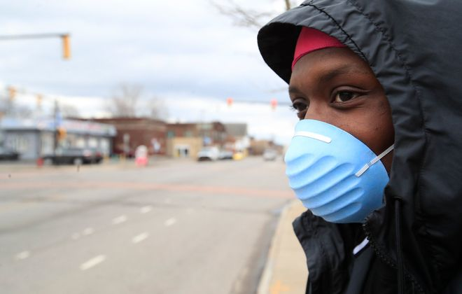 Brandon Laury wears a mask as he waits for a ride along South Park Avenue. (Harry Scull Jr./Buffalo News)