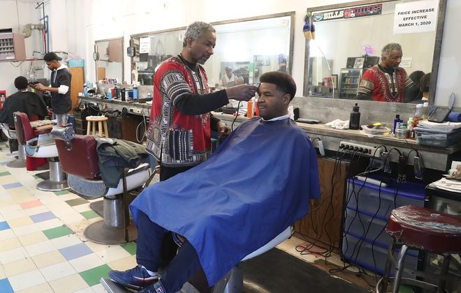 Jerry Daniels Jr. cuts Sheldon Johnson's hair at the Carl-Jeff Barber Shop, on 859 Jefferson Ave. Saturday, the last day of business before all barbershops in the state were ordered close to try to halt the spread of Covid-19. (James P. McCoy/Buffalo News)
