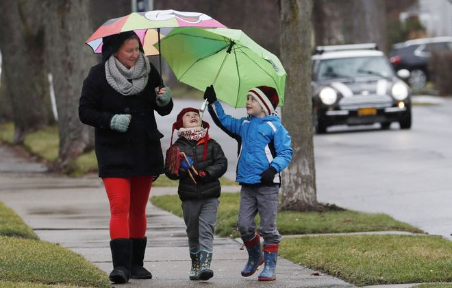 """Teresa Bosch takes a walk in the rain with her sons Mateo, 4, center,  and Lucas, 6, during """"recess"""" from their home-schooling on Parkside Avenue in Buffalo, Monday, March 23, 2020. Bosch is trying to work from home and school her children as well, which she says is proving to be a challenge. (Sharon Cantillon/Buffalo News)"""