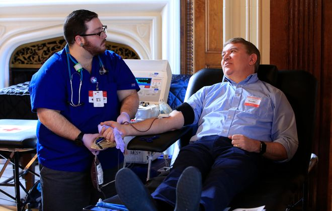 James Cannata, left, a mobile supervisor at with the American Red Cross, handles the blood donation of   Scott Scanlon at the regional headquarters last month. (Harry Scull Jr./Buffalo News)