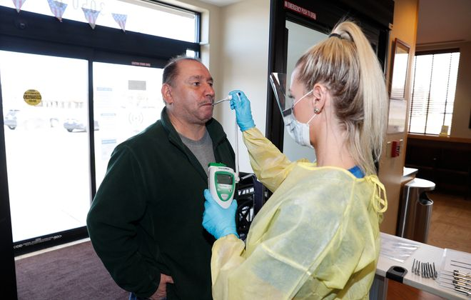 Radiology technologist Jamie Snyder, right, has increased duties beside taking X-rays, including screening patients like Michael Marguccio upon arrival to WNY Immediate Care in Orchard Park on Tuesday, March 24, 2020. (Robert Kirkham/Buffalo News)