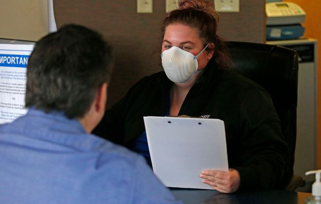 Patient service representative Kendra Feldmann sits face to face as she registers arriving patients upon their arrival. This was at WNY Immediate Care at 3050 Orchard Park Rd. in Orchard Park on Wednesday, March 25, 2020. (Robert Kirkham/Buffalo News)