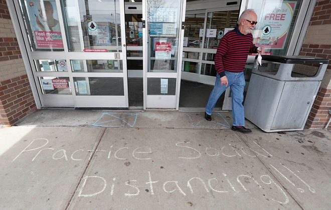 A message for safe social distancing is written in chalk in the front of Walgreens on Hertel Avenue in Buffalo as Sam Granelli exits the store, Thursday, March 26, 2020. (Sharon Cantillon/Buffalo News)